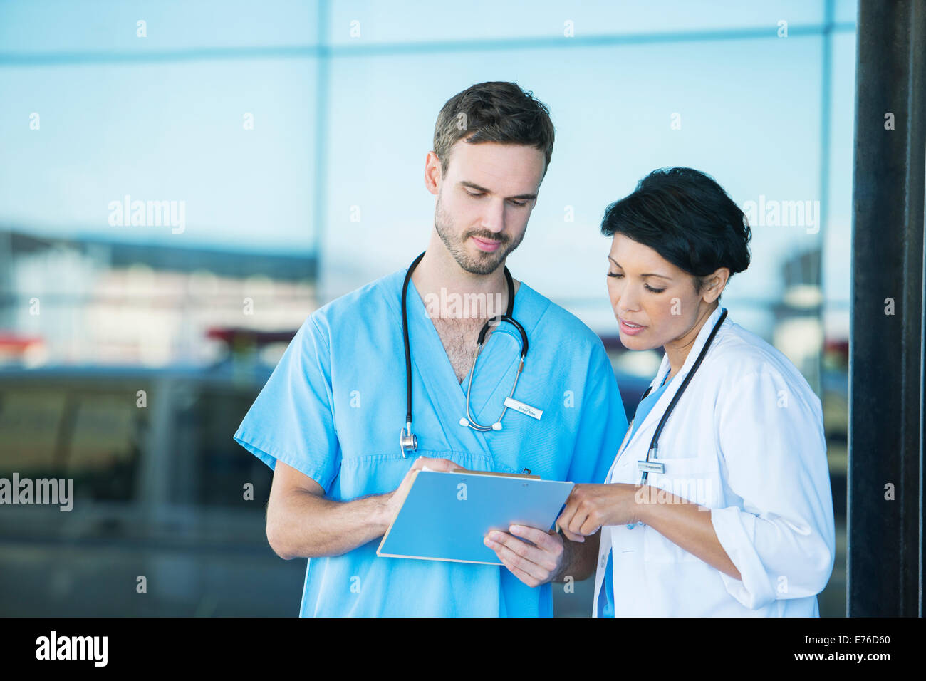 Doctor and nurse reading medical chart outdoors - Stock Image
