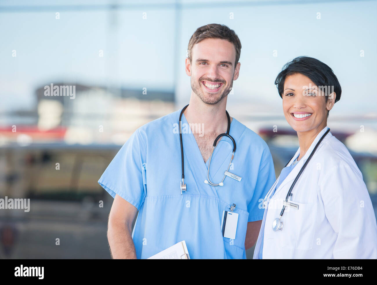 Doctor and nurse smiling outdoors - Stock Image