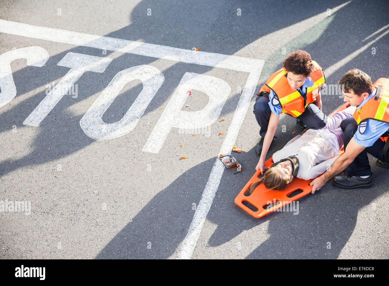 Paramedics examining injured girl on street - Stock Image