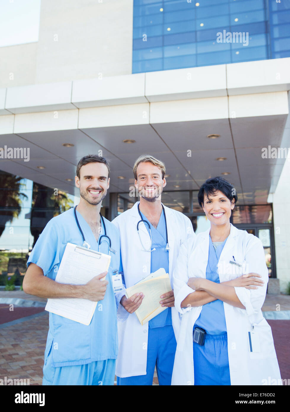 Doctors and nurse smiling outside hospital - Stock Image