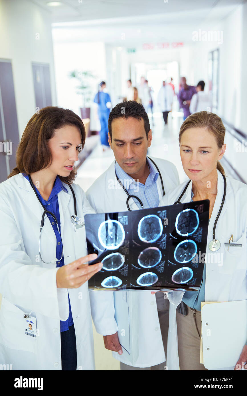 Doctors examining x-rays in hospital hallway - Stock Image