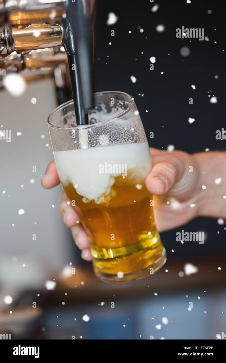Composite image of hand holding glass filling beer - Stock Image