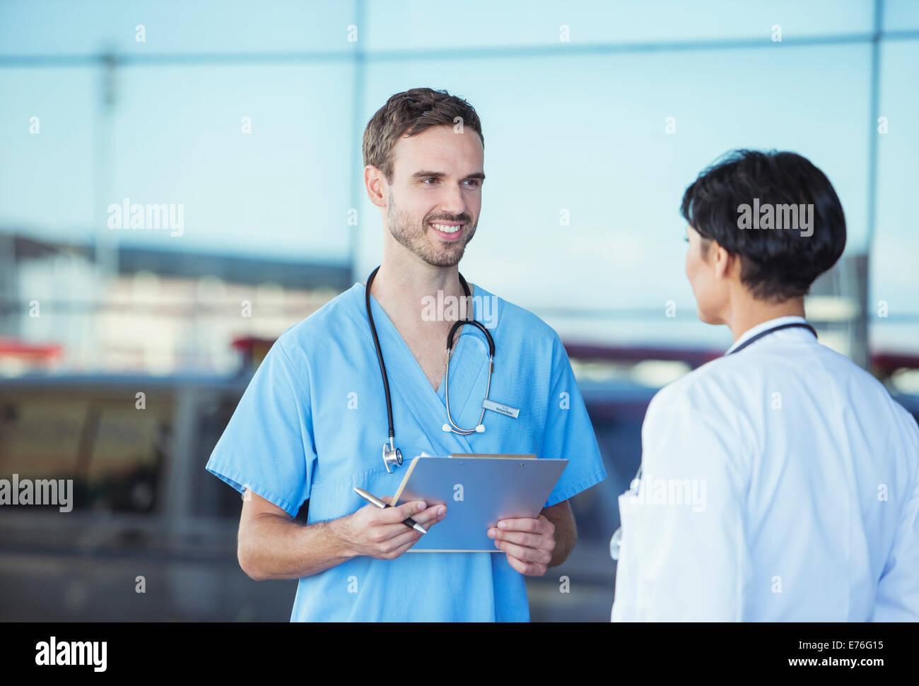 Doctor and nurse talking outside hospital - Stock Image