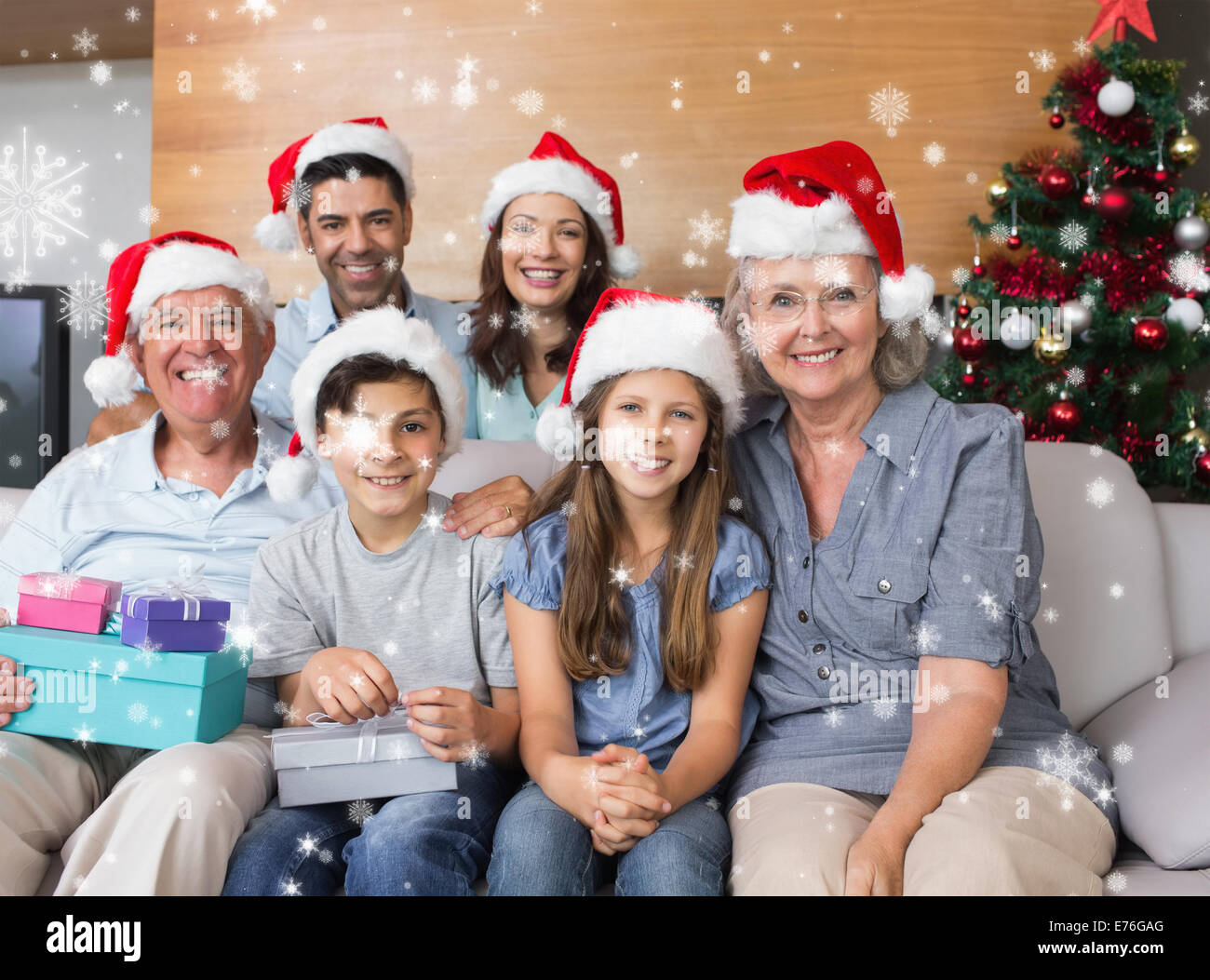 Composite image of extended family in christmas hats with gift boxes in living room - Stock Image