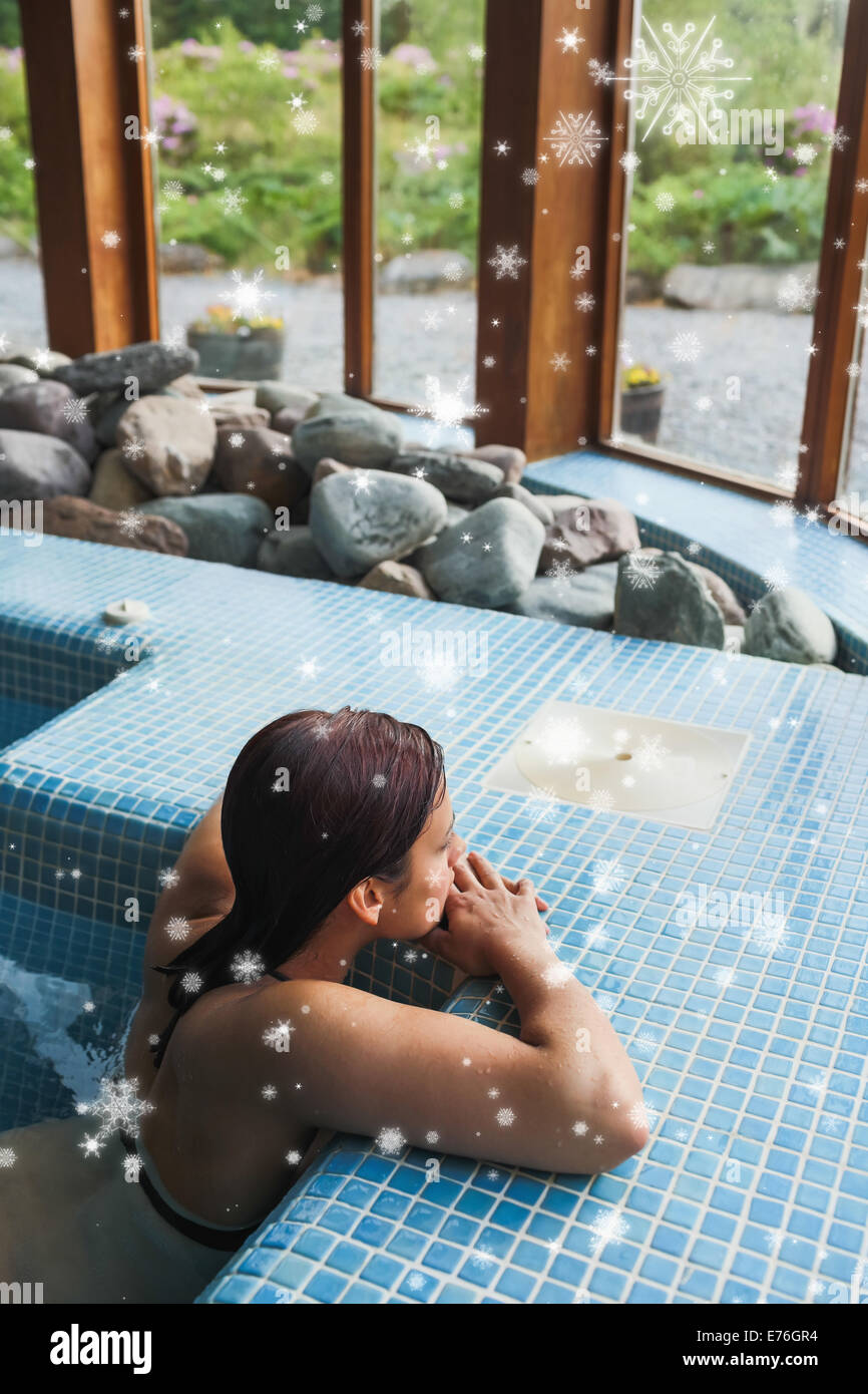 Composite image of brunette relaxing in a jacuzzi - Stock Image