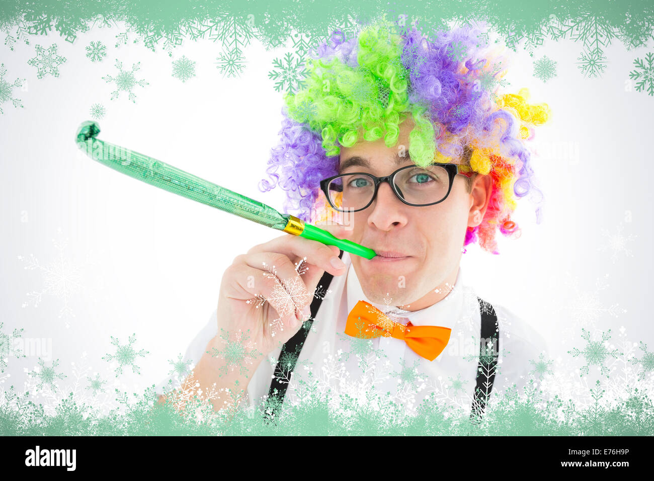 Composite image of geeky hipster wearing a rainbow wig blowing party horn Stock Photo