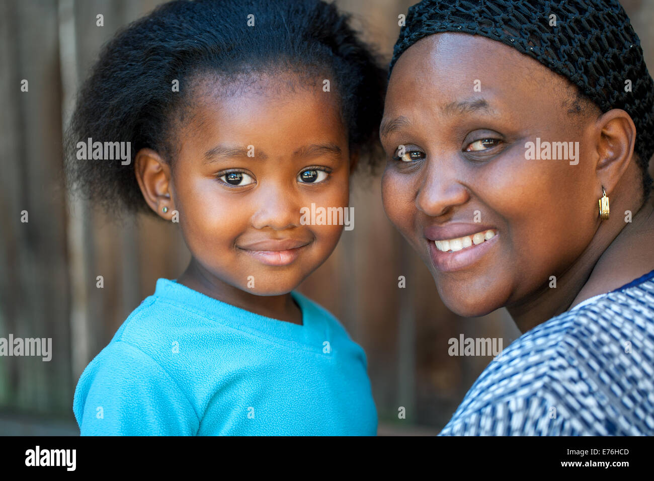 Face shot of little African girl with mom outdoors. - Stock Image