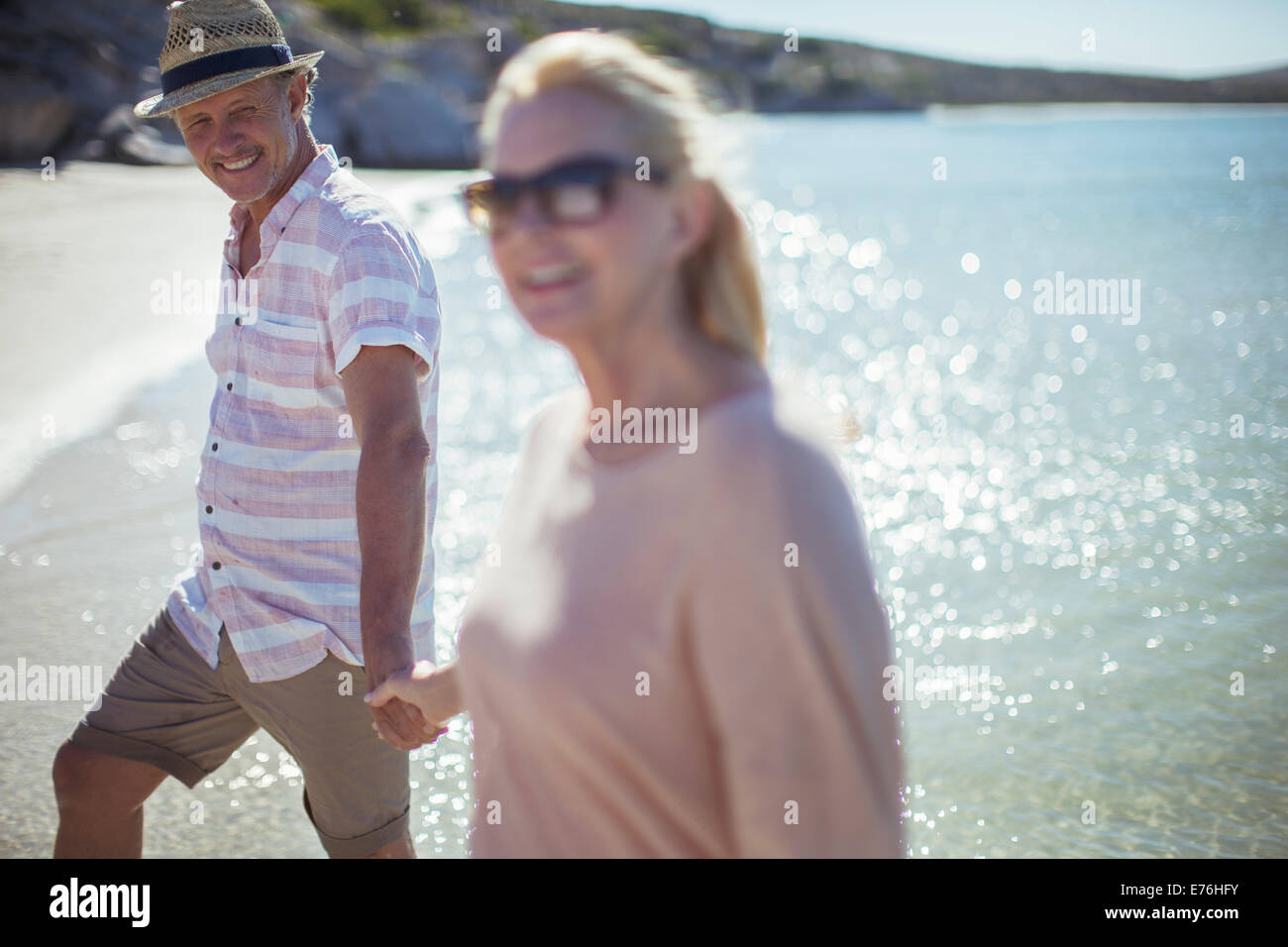 Couple holding hands on beach - Stock Image