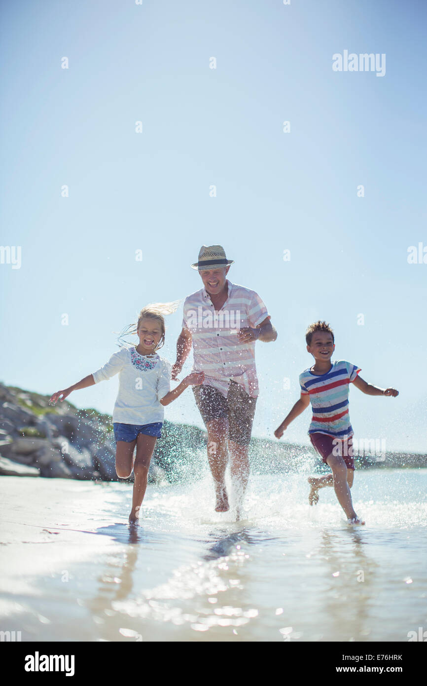 Family running in water on beach - Stock Image