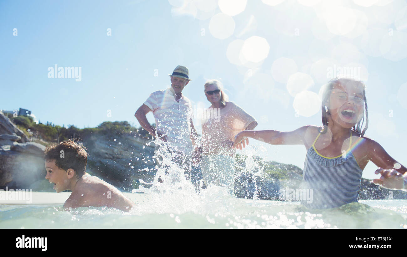Family splashing each other on beach - Stock Image