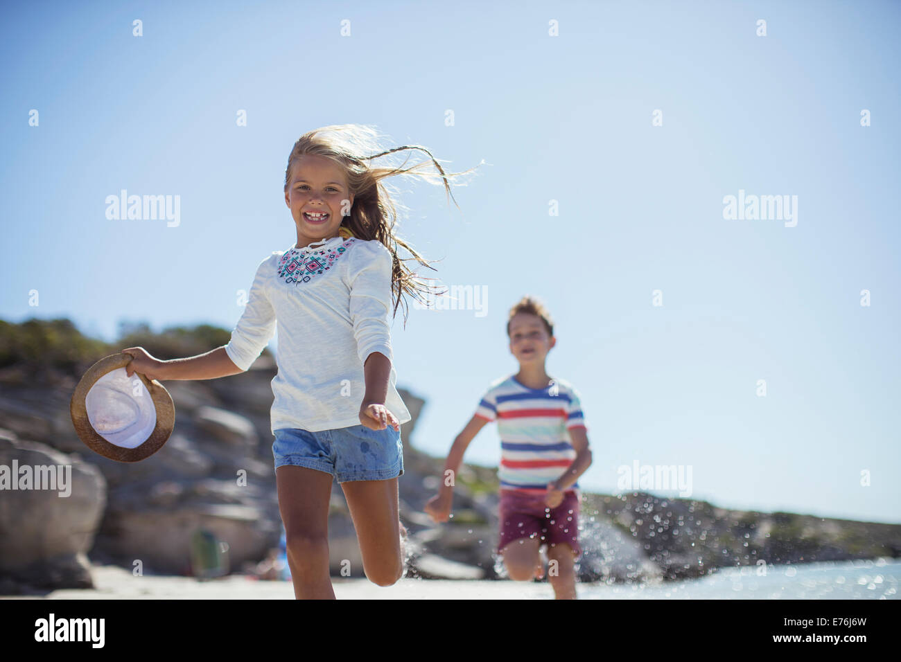 Young girl and boy running along beach Stock Photo