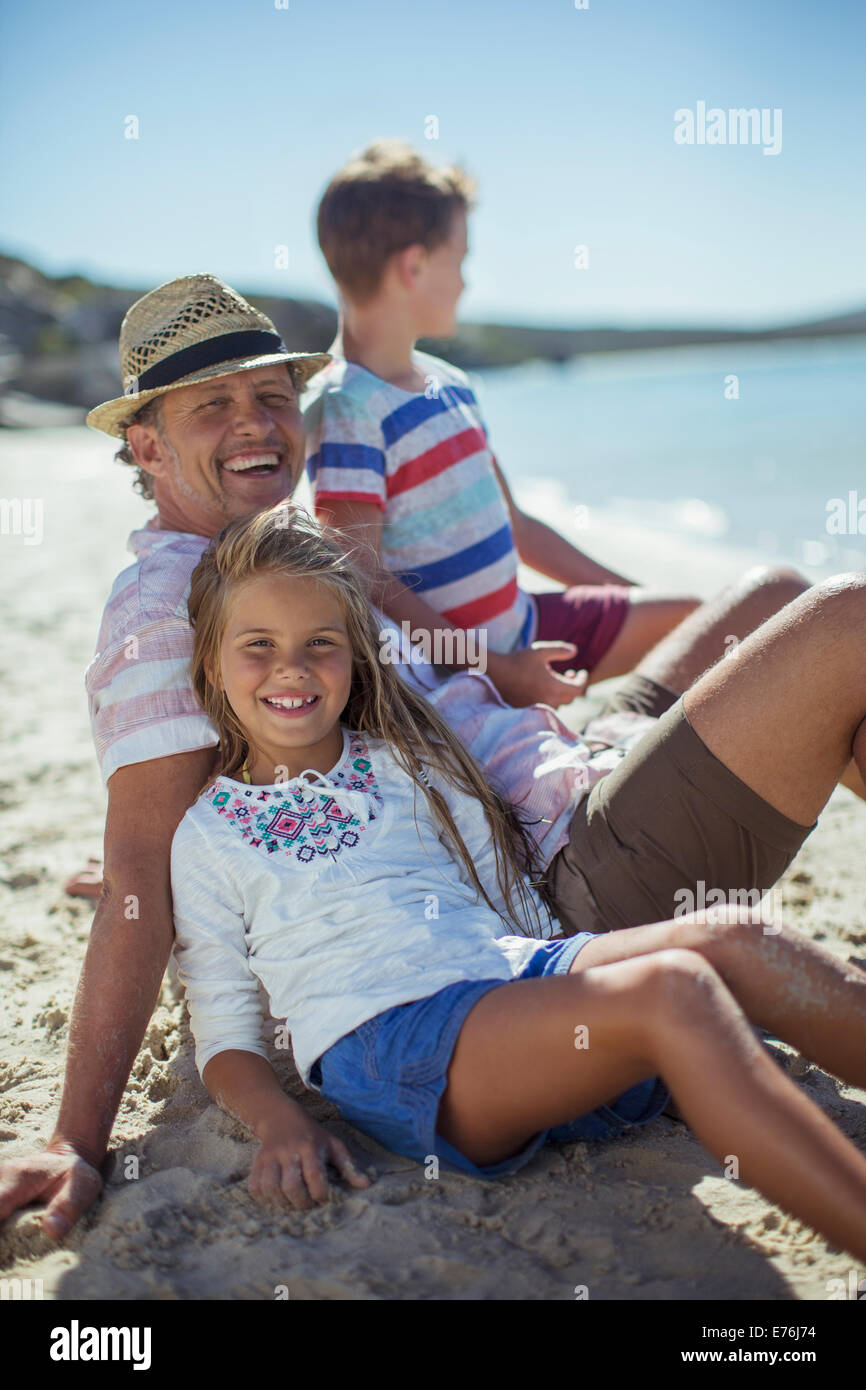 Family sitting in sand together Stock Photo