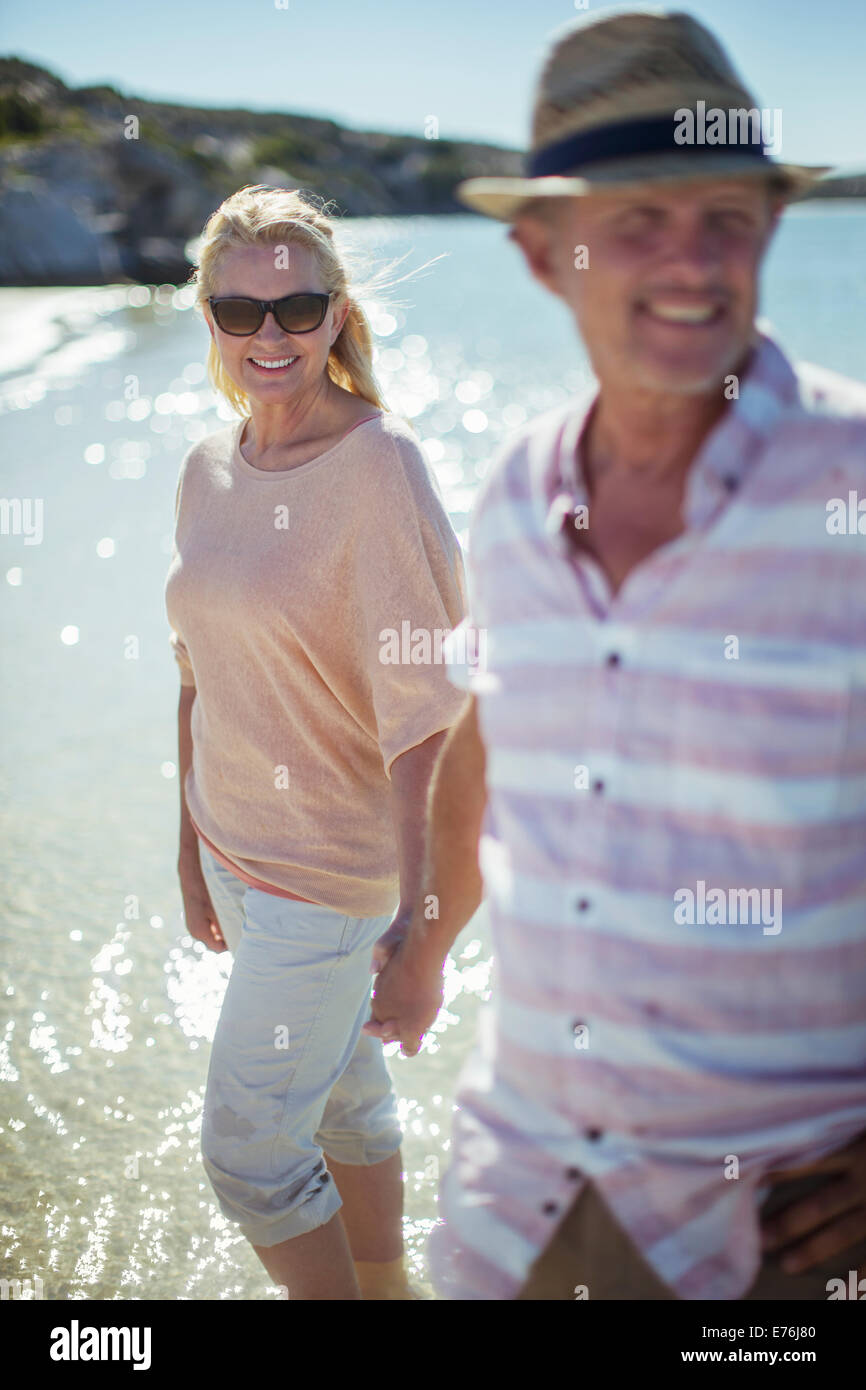 Couple walking in water together - Stock Image