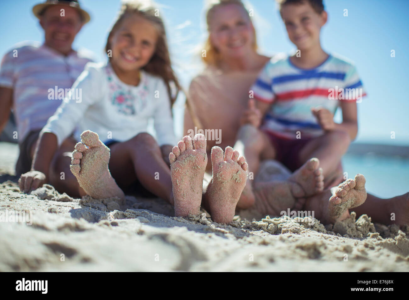 Family sitting together with feet in sand - Stock Image
