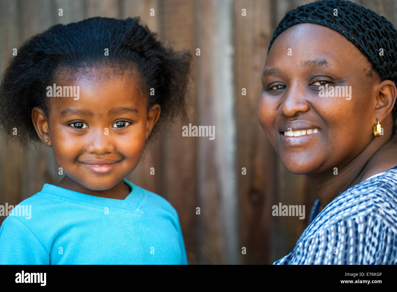 Portrait of cute African girl next to mother. - Stock Image