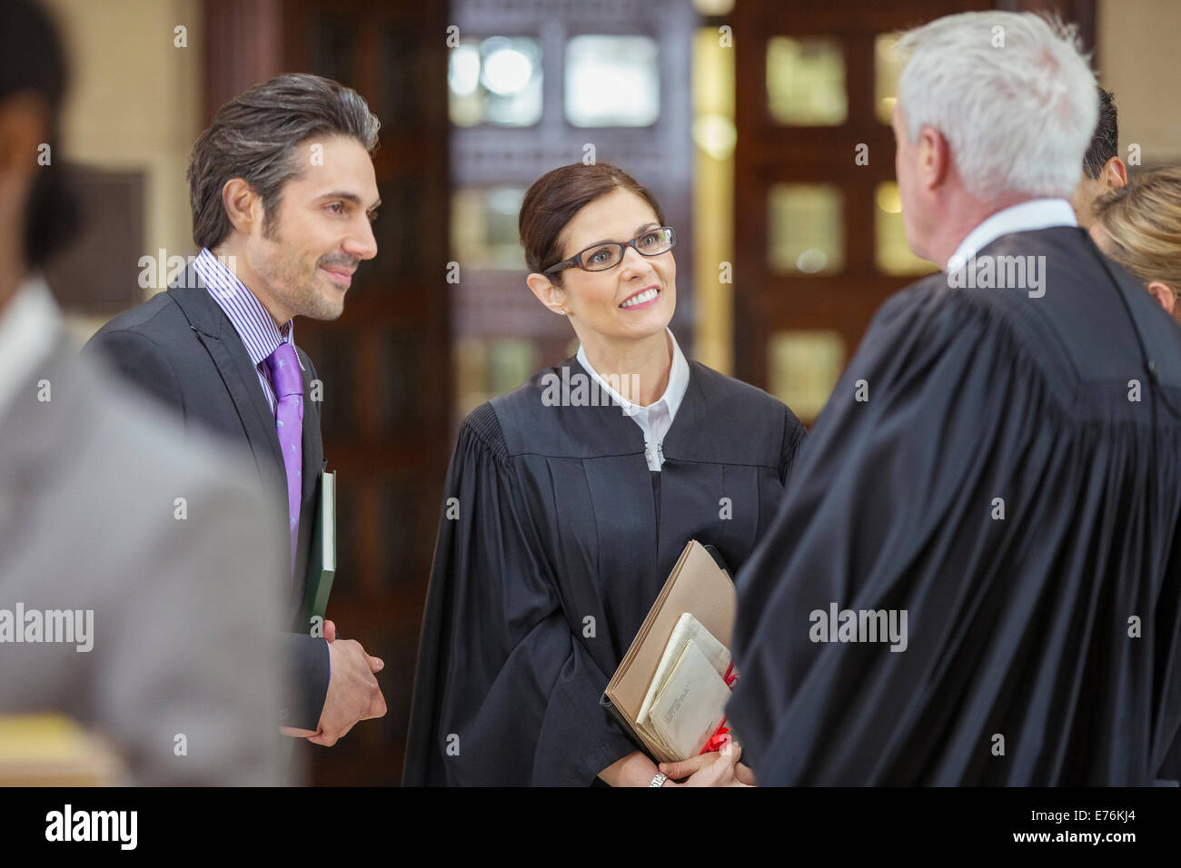 Judges and lawyers talking outside courtroom - Stock Image