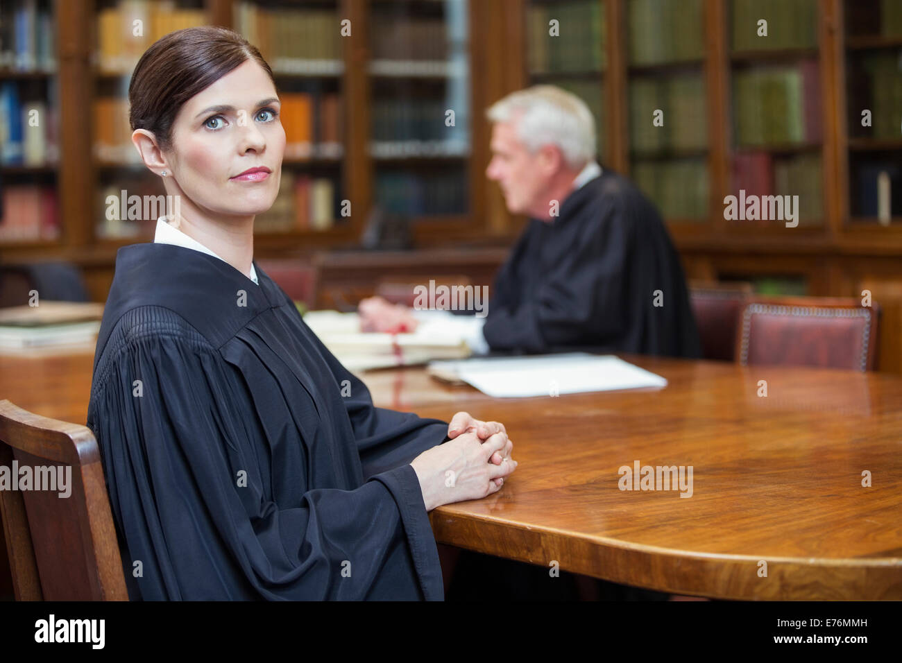 Lawyer sitting at meeting table in chambers - Stock Image
