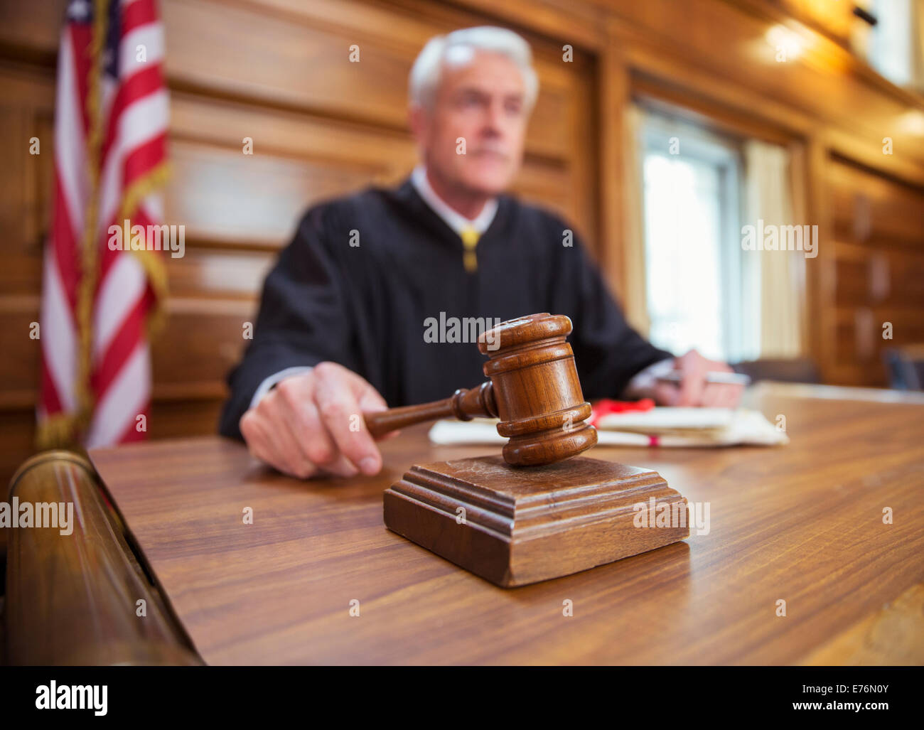 Judge holding gavel in court - Stock Image