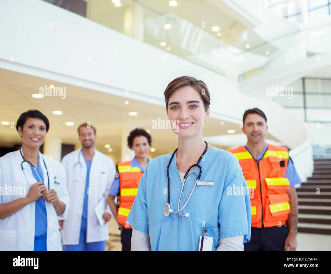 Doctors, nurses and paramedics smiling in hospital Stock Photo
