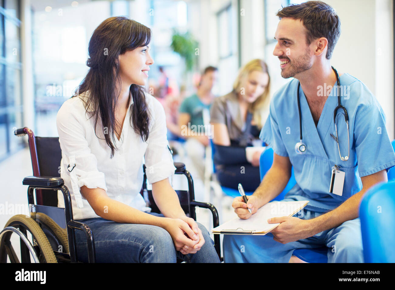 Patient in wheelchair talking to nurse in hospital - Stock Image