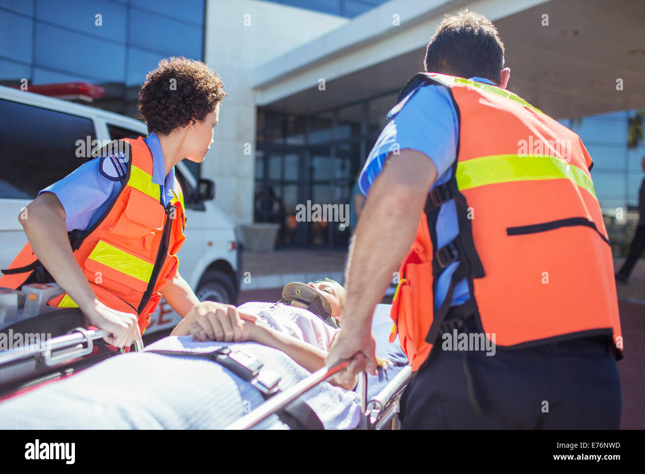 Paramedics wheeling patient in hospital parking lot - Stock Image