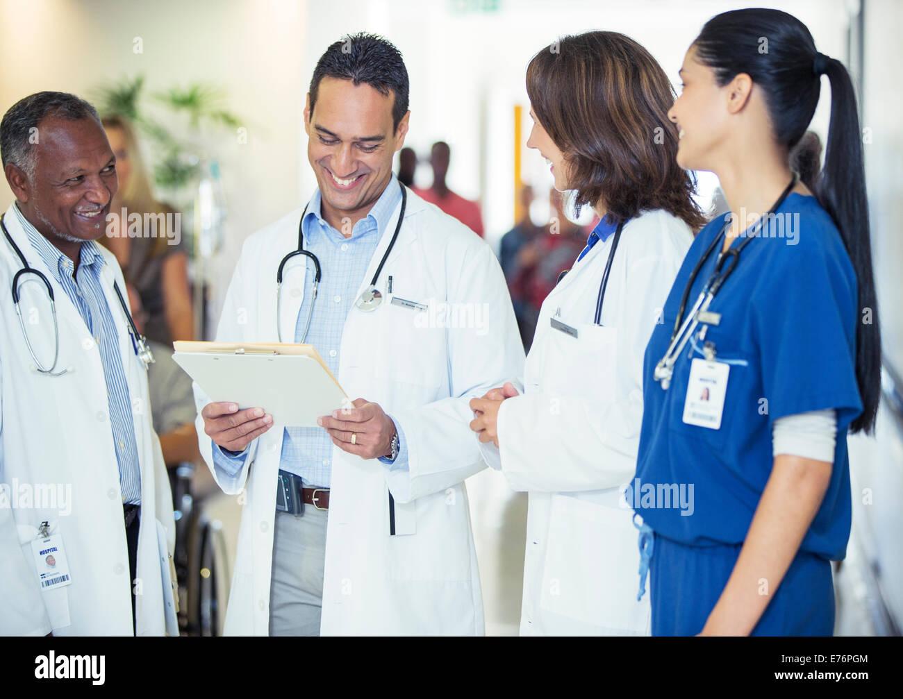 Doctors and nurse talking in hospital hallway Stock Photo