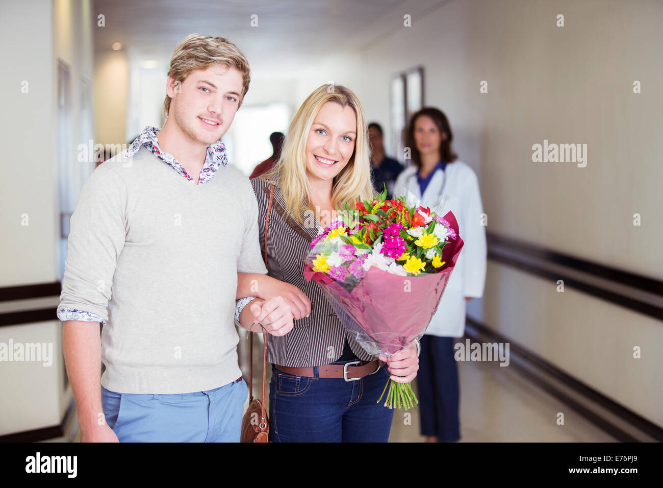 Couple carrying bouquet of flowers in hospital Stock Photo