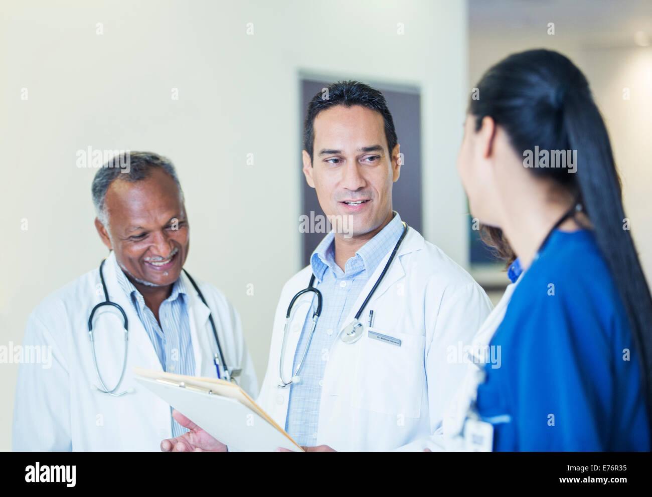 Doctors and nurse talking in hospital hallway - Stock Image