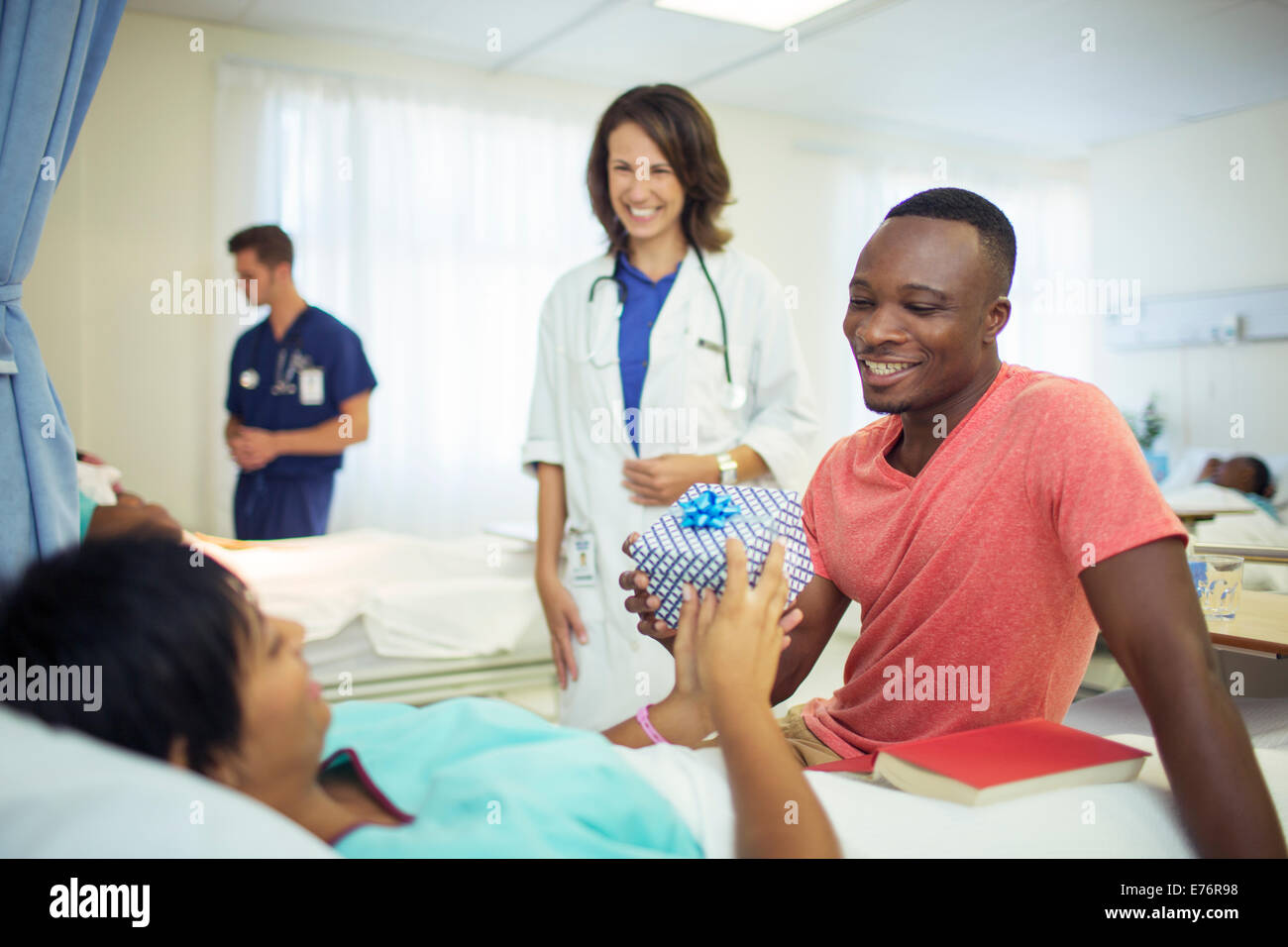 Man giving girlfriend present in hospital - Stock Image