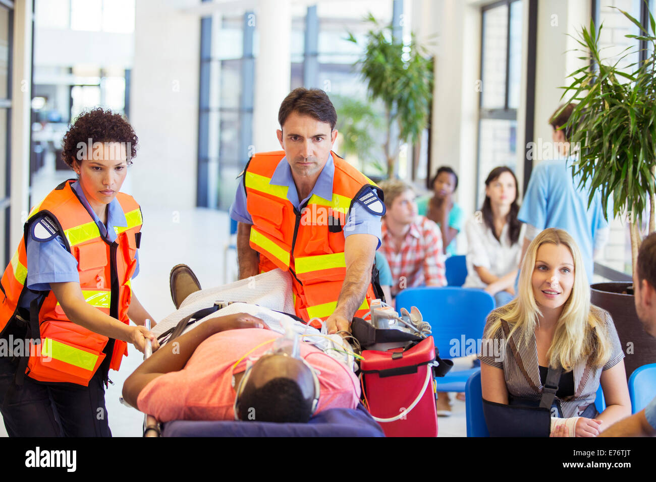 Paramedics wheeling patient in hospital - Stock Image