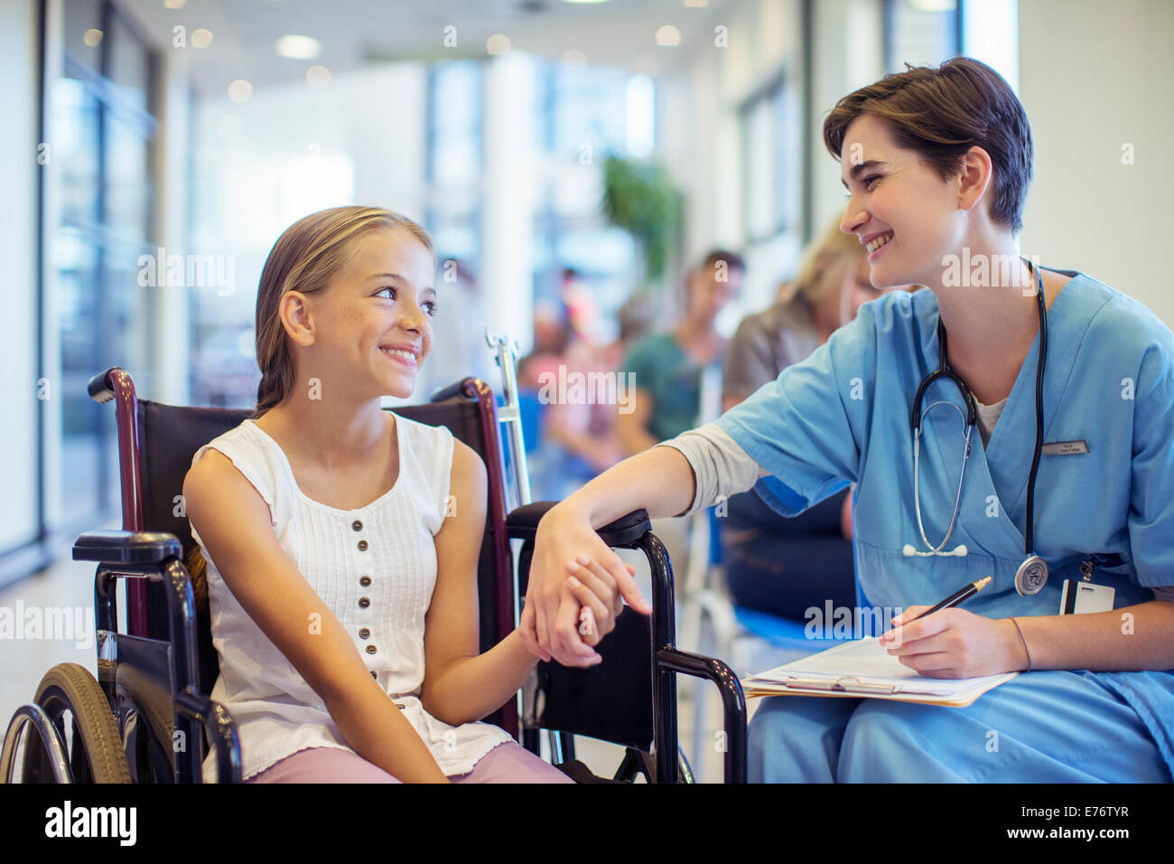 Nurse holding patient's hands in hospital - Stock Image