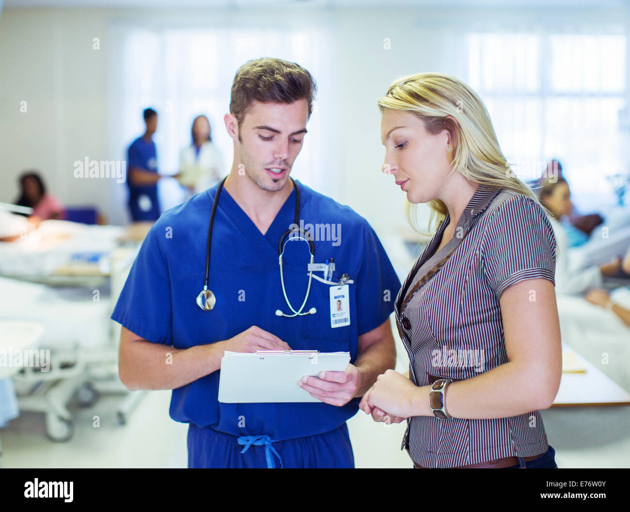 Nurse and patient reading medical charts in hospital - Stock Image