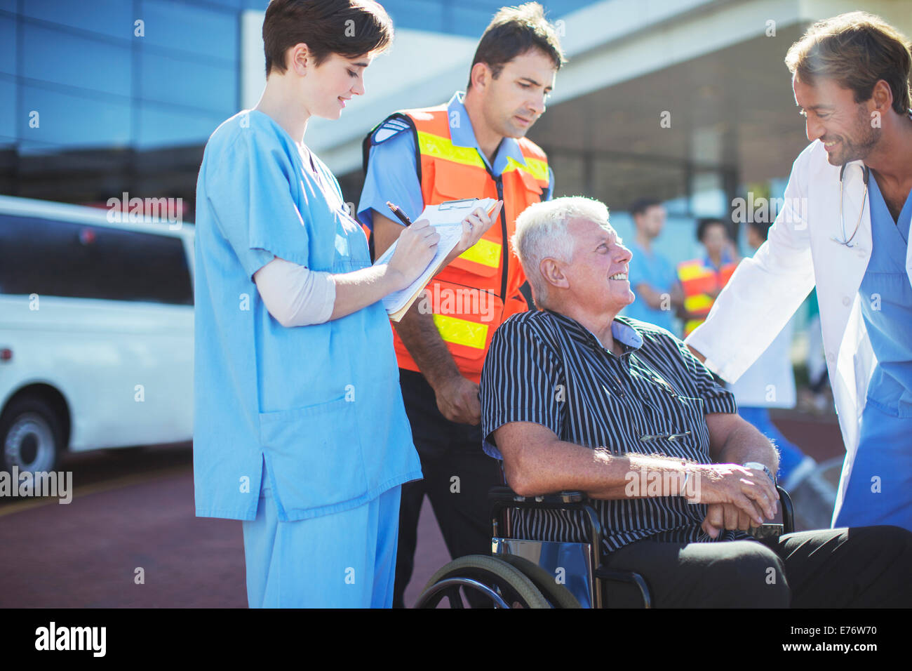 Doctor, nurse and paramedic talking to patient outside hospital - Stock Image