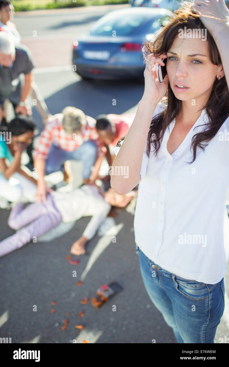Woman calling emergency services at car accident - Stock Image