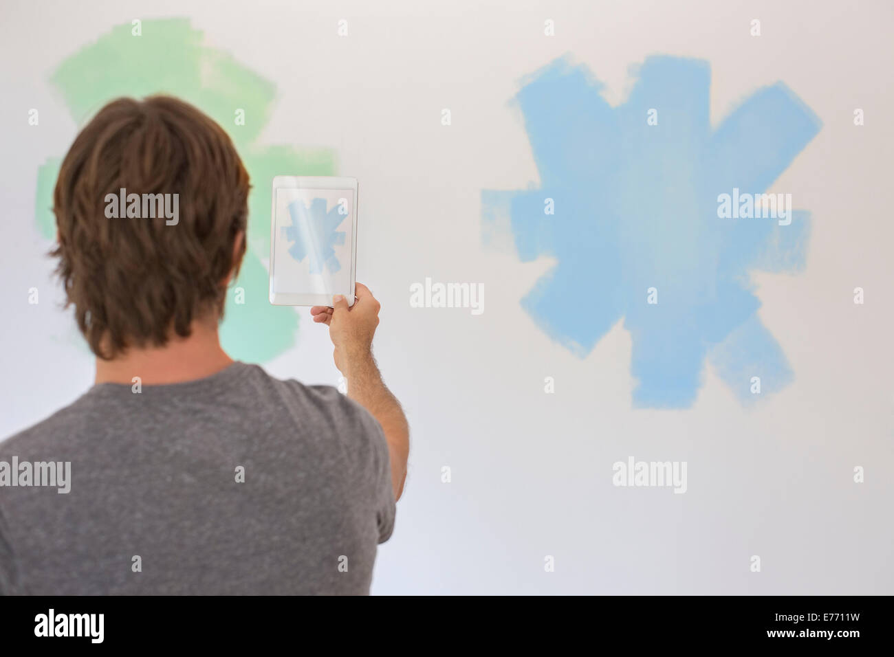 Man taking photo of wall with digital tablet - Stock Image