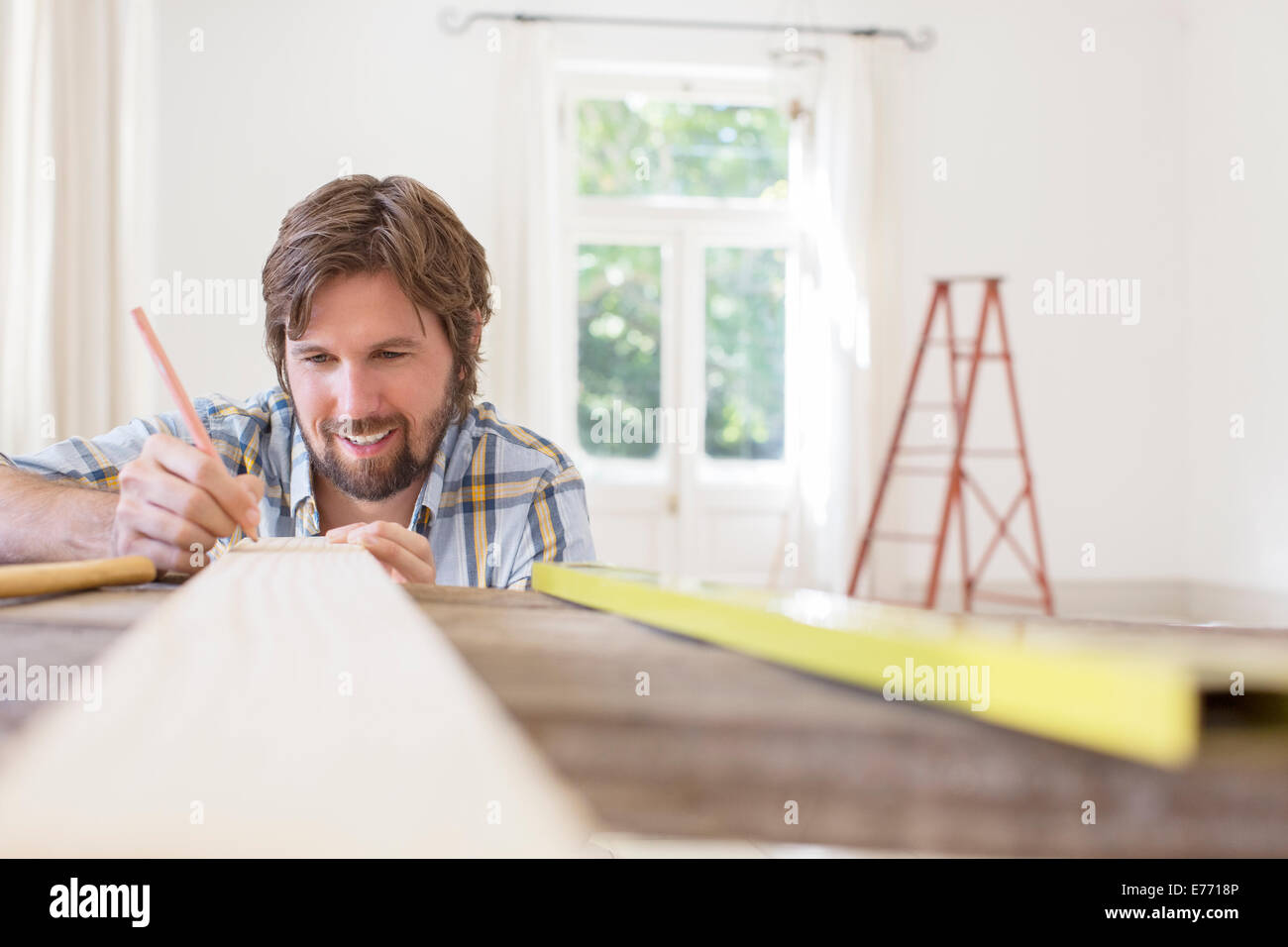 Man marking wood in living area - Stock Image