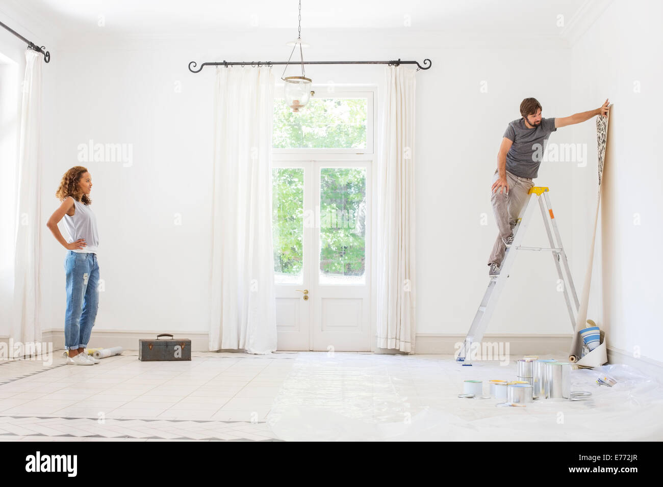 Couple hanging wallpaper together - Stock Image