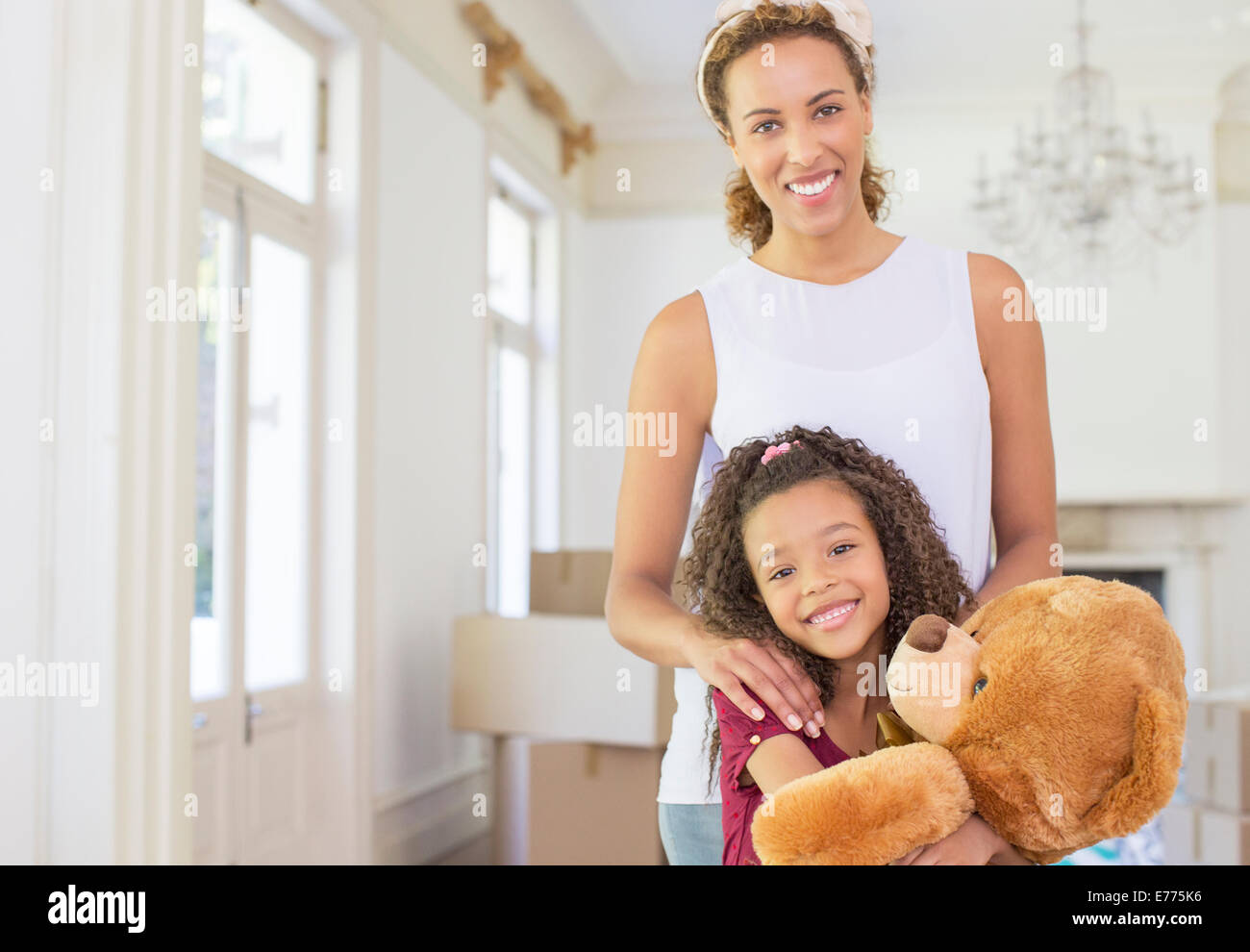 Mother and daughter smiling while clutching teddy bear - Stock Image