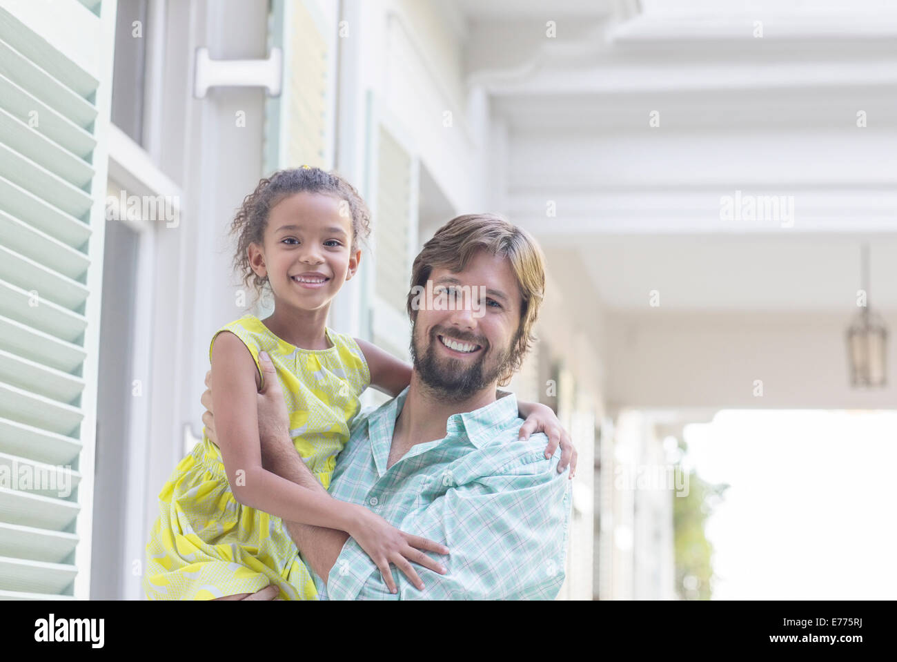 Father holding daughter in arms outdoors - Stock Image