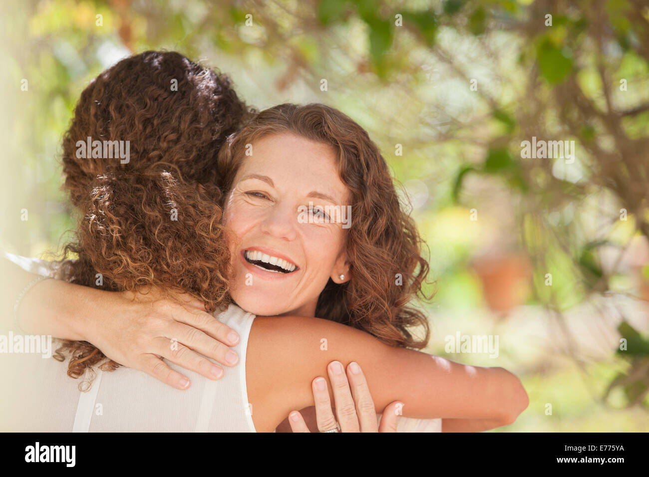 Mother and daughter hugging outdoors - Stock Image