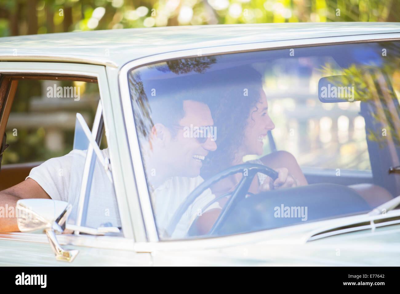 Couple enjoying car ride on sunny day - Stock Image