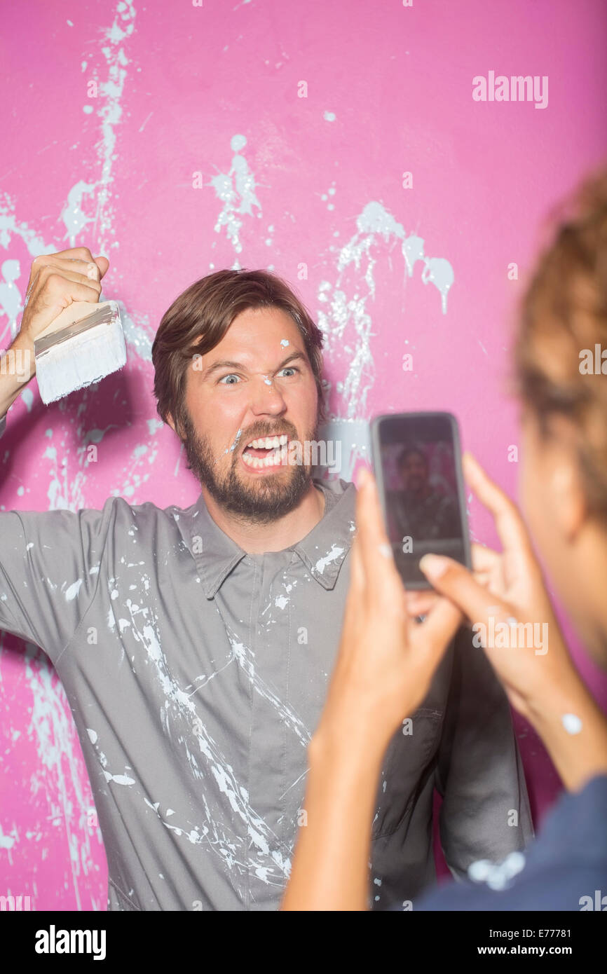 Woman taking picture with cell phone of man with paintbrush - Stock Image