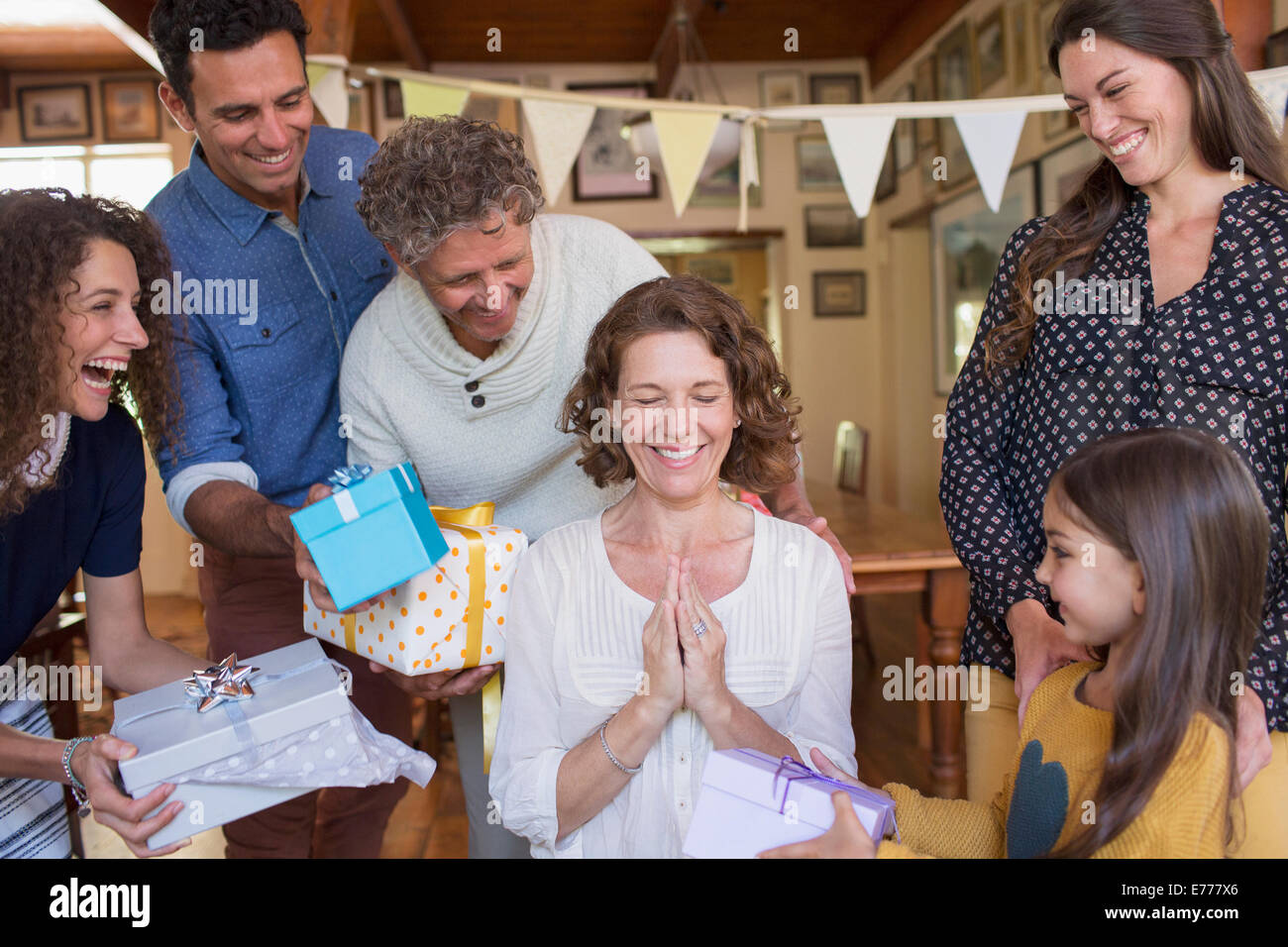 Older woman being given gift by family - Stock Image