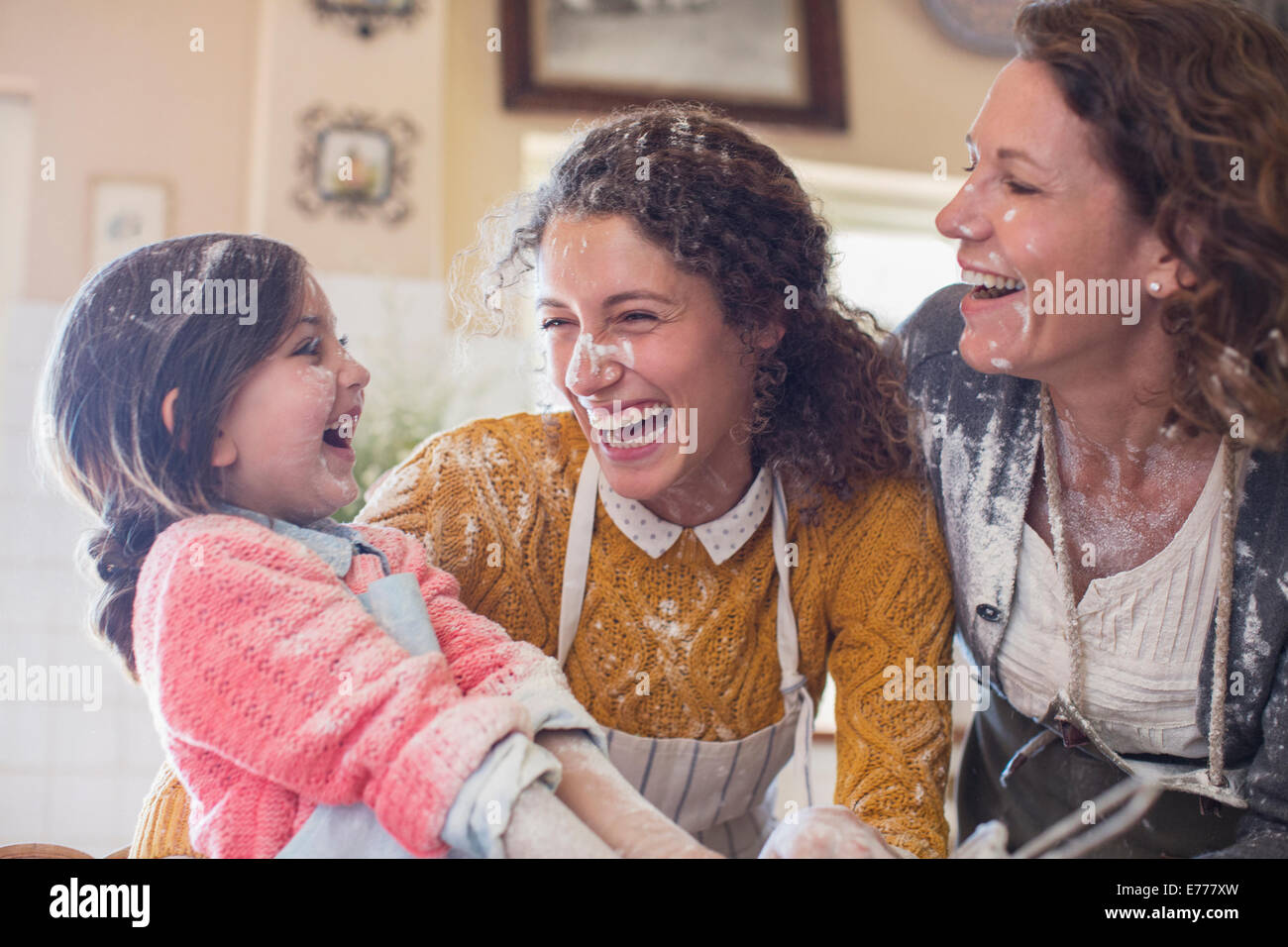Three generations of women playing in the kitchen - Stock Image
