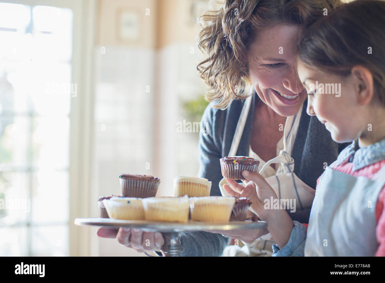 Grandmother offering granddaughter cupcakes - Stock Image