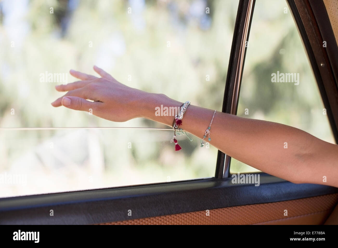 Woman feeling wind on her hand through car window - Stock Image