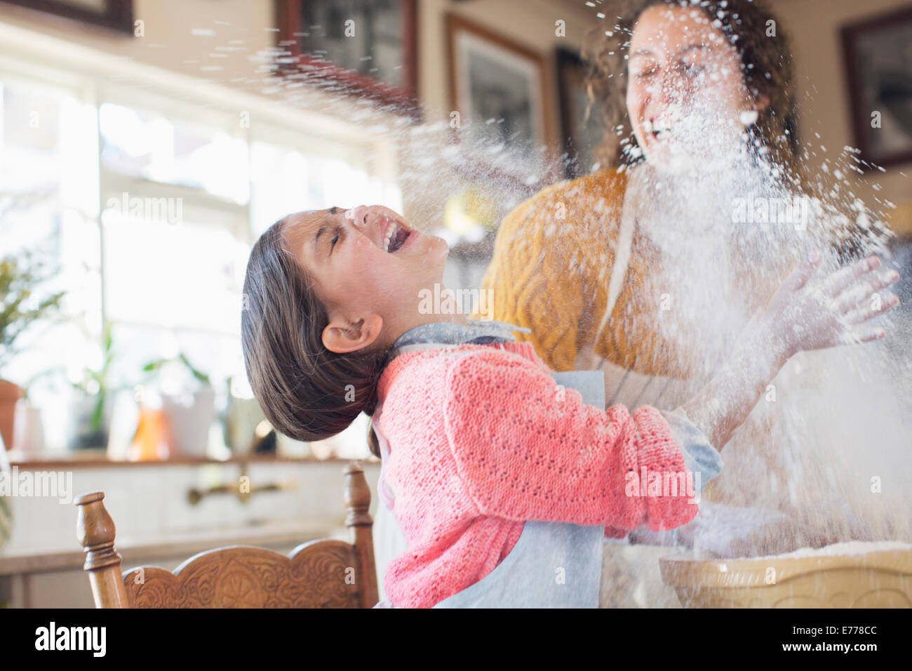 Mother and daughter playing with flour in the kitchen - Stock Image