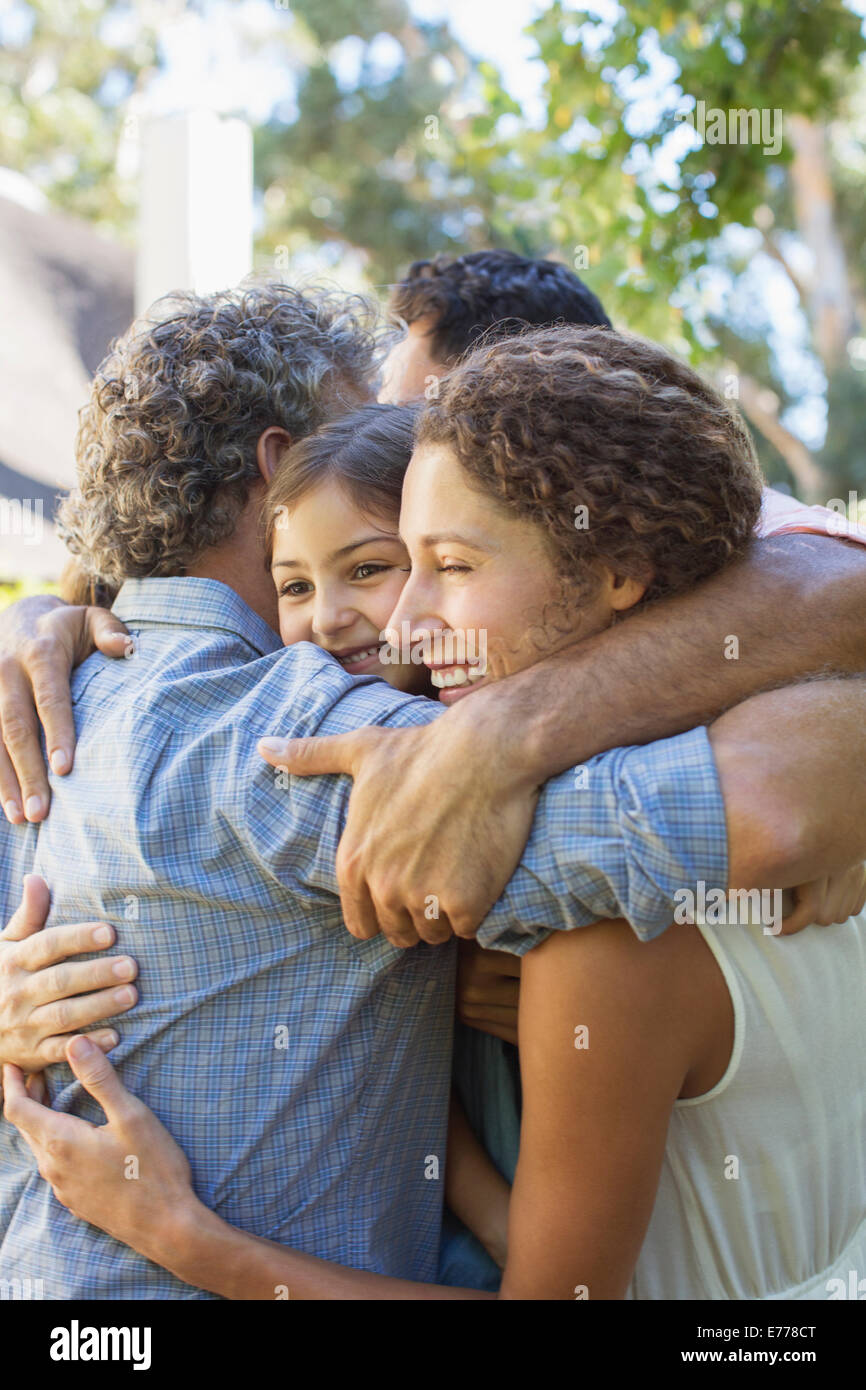 Family hugging outdoors - Stock Image