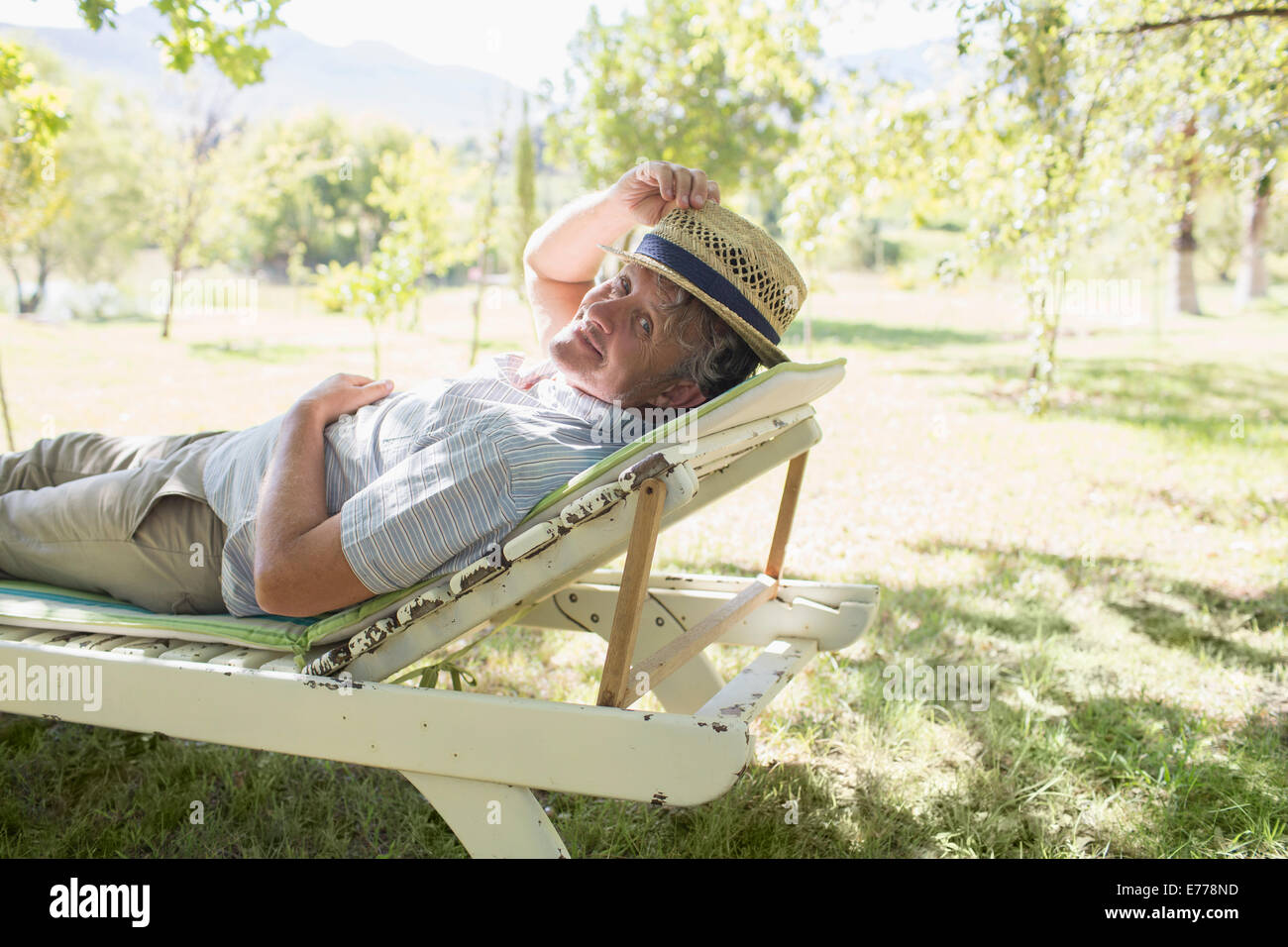 Older man relaxing on lawn chair outdoorsStock Photo