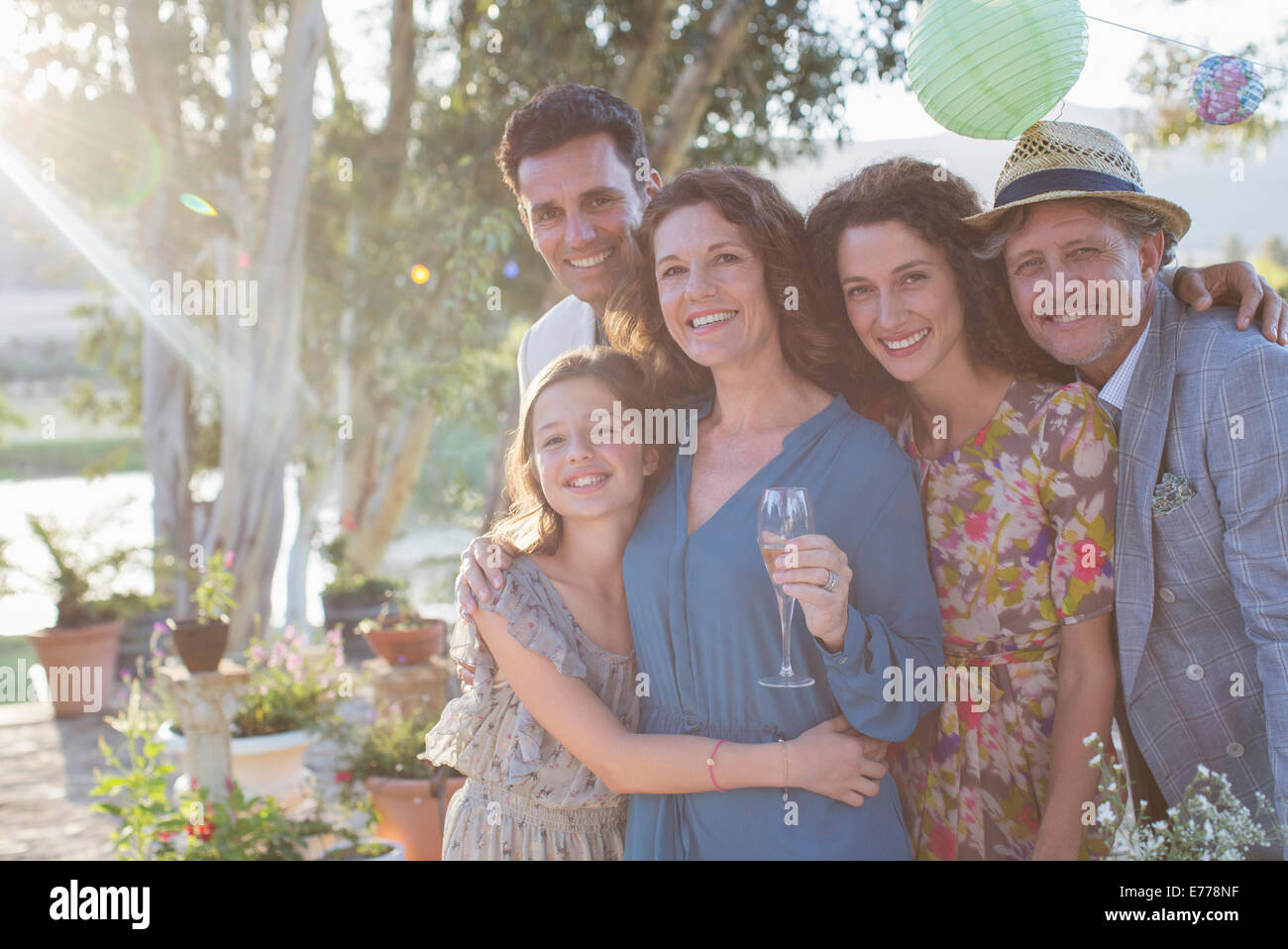 Family hugging outdoors on sunny day - Stock Image